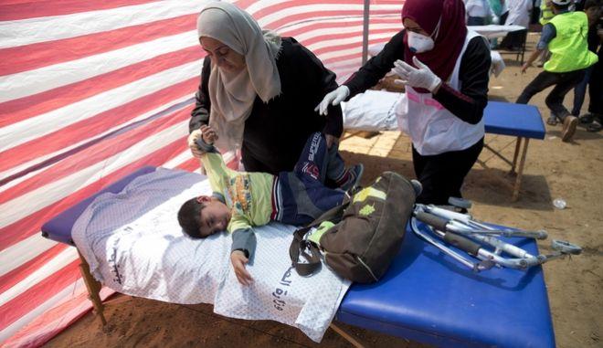 Παλαιστίνια κρατά το παιδί της που υποφέρει από εισπνοή δακρυγόνων μετά την επίθεση του Ισραηλινού στρατού κατά διαδηλωτών στη λωρίδα της Γάζας, που διαμαρτύρονταν για τη μεταφορά της πρεσβείας των ΗΠΑ στην Ιερουσαλήμ