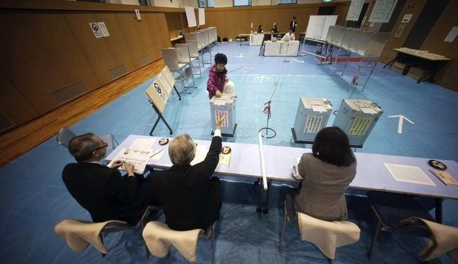 A voter casts her ballot in general election at a polling station in Tokyo Sunday, Oct. 22, 2017. Voting has kicked off for Japans general election on Sunday that would most likely hand Prime Minister Shinzo Abes ruling coalition a win, possibly retaining two-thirds in the parliament. (AP Photo/Eugene Hoshiko)