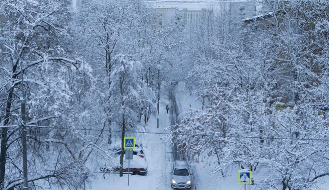 A car drives along a street during heavy snowfall in Moscow, Russia, Sunday, Feb. 4, 2018. Heavy snow and freezing rain have knocked down thousands of trees in the Russian capital and one person is reported to have been killed. (AP Photo/Alexander Zemlianichenko Jr )