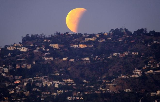 A super blue blood moon is seen setting behind the Hollywood hills in Los Angeles on Wednesday Jan. 31, 2018. The moon is putting on a rare cosmic show. It's the first time in 35 years a blue moon has synced up with a supermoon and a total lunar eclipse. NASA is calling it a lunar trifecta: the first super blue blood moon since 1982. That combination won't happen again until 2037. (AP Photo/Richard Vogel)
