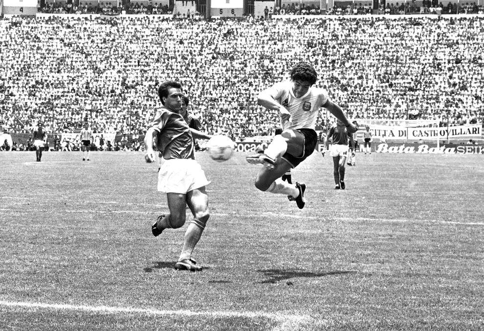 Ο Ντιέγο Μαραντόνα σουτάρει μπροστά στον Γκαετάνο Σιρέα και ισοφαρίζει σε 1-1 την αναμέτρηση της Αργεντινής με την Ιταλία στους ομίλους (5/6/1986).