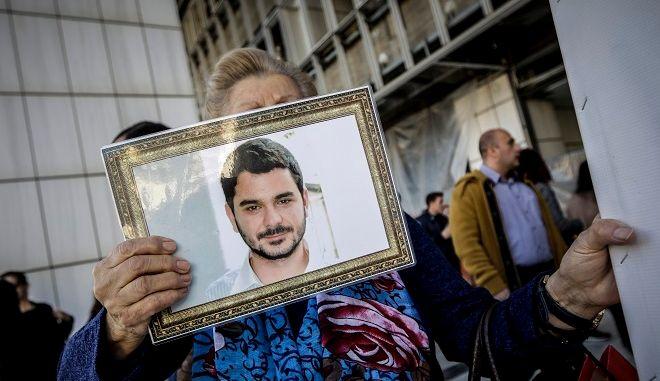 Συγγενείς του Μάριου Παπαγεωργίου κρατώντας πλακάτ και φωτογραφίες είναι συγκεντρωμένοι έξω από το Μεικτό Ορκωτό Εφετείο Αθηνών.