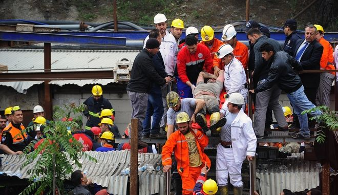 Rescue workers carry a rescued miner to an ambulance outside the mine in Soma, western Turkey, Wednesday, May 14, 2014. An explosion and fire at the coal mine killed at least 232 workers, authorities said, in one of the worst mining disasters in Turkish history. Turkey's Energy Minister Taner Yildiz said 787 people were inside the coal mine at the time of the accident. (AP Photo/Emre Tazegul)