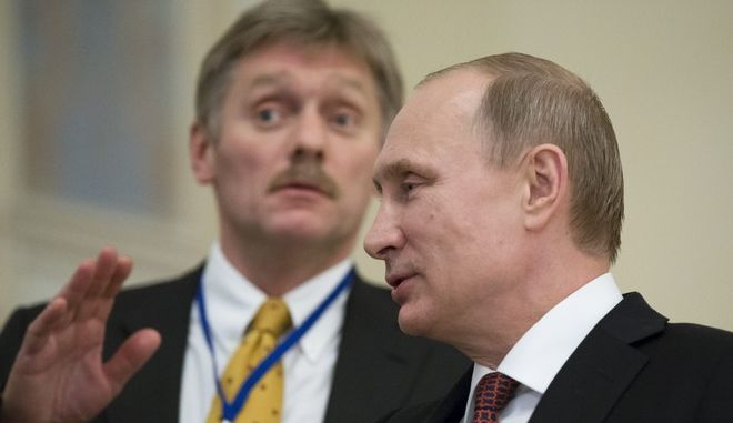 In this photo taken on Thursday, Feb.  12, 2015, Russian President Vladimir Putin,  right, speaks to a journalist as his press secretory  Dmitry Peskov tries to stop questions after the peace talks in Minsk, Belarus, Thursday, Feb. 12, 2015.  Peskov told The Associated Press that Putins health is really perfect, dismissing media speculation that the president could be unwell.  (AP Photo/Alexander Zemlianichenko)
