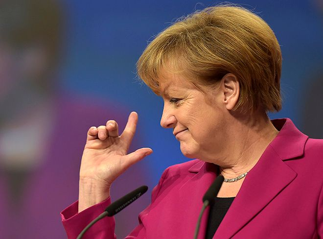 German Chancellor and chairwoman of the German Christian Democrats, CDU, Angela Merkel, points with her fingers during a visit to the  convention venue prior to  the 27. party convention in Cologne, Germany, Monday, Dec. 8, 2014. (AP Photo/Martin Meissner)
