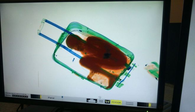 In this photo released by the Spanish Guardia Civil on Friday, May 8, 2015, a boy curled up inside a suitcase is seen on the display of a scanner at the border crossing in Ceuta, a Spanish city enclave in North Africa. A Spanish court has ordered the detention of a father who allegedly hid his 8-year-old son inside a closed suitcase in an attempt to smuggle the child illegally into Europe. A police statement said guards stopped a 19-year-old Moroccan woman who looked nervous as she waited in line Thursday at the land border crossing in Ceuta (AP Photo/Spanish Interior Ministry, via AP)