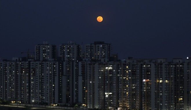 A full moon rises from behind residential buildings in Greater Noida, a suburb of New Delhi, India, Thursday, May 7, 2020. (AP Photo/Altaf Qadri)