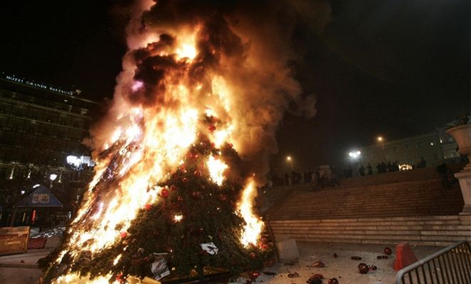 Athens' giant Christmas tree burns in front of the Greek parliament in Athens December 8, 2008. Protesters set fire to a major department store in central Athens and torched the city's giant Christmas tree outside parliament as anti-government protests worsened. REUTERS/John Kolesidis  (GREECE)