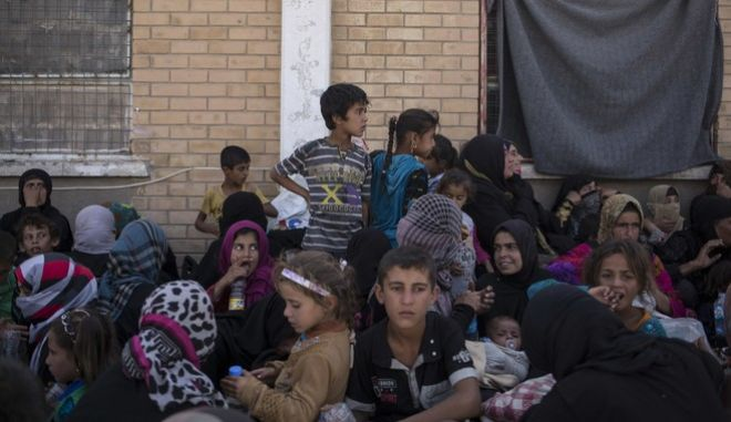 FILE - In this Tuesday, Oct. 3, 2017 file photo, women and children from Hawija sit outside a Kurdish screening center in Dibis, Iraq. On Thursday Iraqi Prime Minister Haider al-Abadi troops have driven IS militants from the town of Hawija, one of the extremists last strongholds in the country. The announcement comes amid a political crisis following a controversial Kurdish independence referendum, but on the battlefield at least, Iraq's army continues to work together with Kurdish peshmerga fighters to keep IS on the back foot.(AP Photo/Bram Janssen, File)