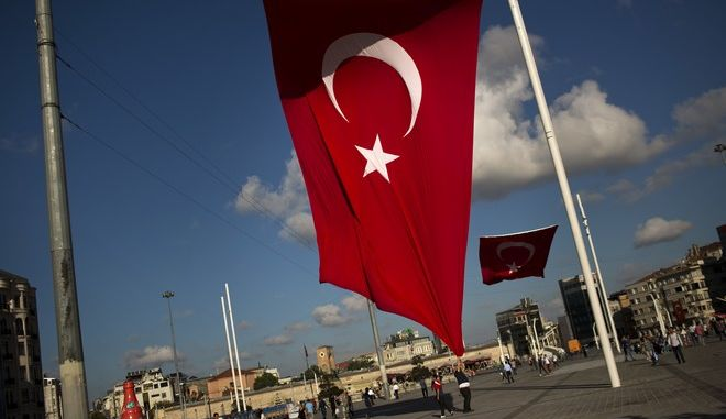 A man grabs a Turkish flag at Taksim Square in central Istanbul, Tuesday, July 19, 2016. Turkey's state-run news agency says courts have ordered 85 generals and admirals jailed pending trial over their roles in a botched coup attempt. Dozens of others were still being questioned. (AP Photo/Emilio Morenatti)