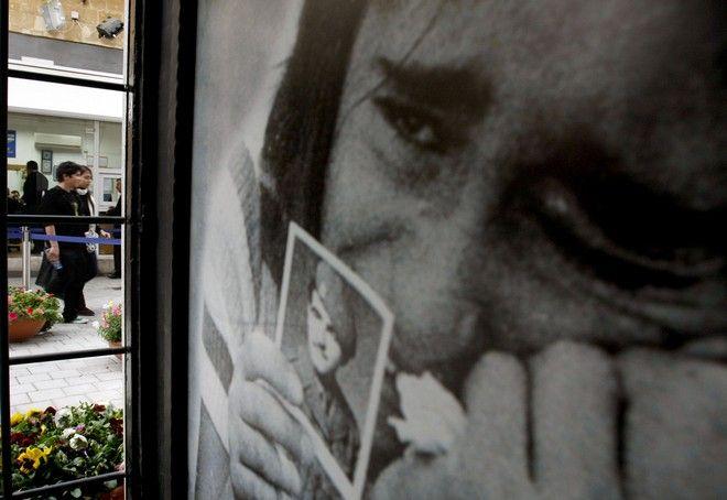 Ελληνοκύπρια κρατά φωτογραφία με τους αγνοούμενους γονείς της