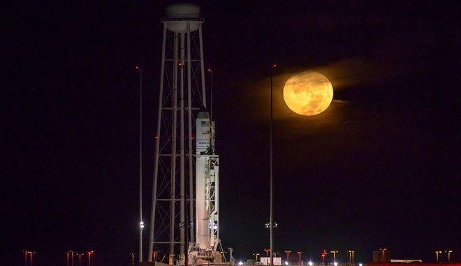 The Orbital ATK Antares rocket, with the Cygnus spacecraft onboard, sits on launch Pad-0A as the moon sets,  Saturday, Oct. 15, 2016 at NASA's Wallops Flight Facility in Virginia.  Two years after a launch explosion, the space company Orbital ATK is returning to Virginia's spaceport to send a load of supplies to the International Space Station.  (Bill Ingalls/NASA via AP)