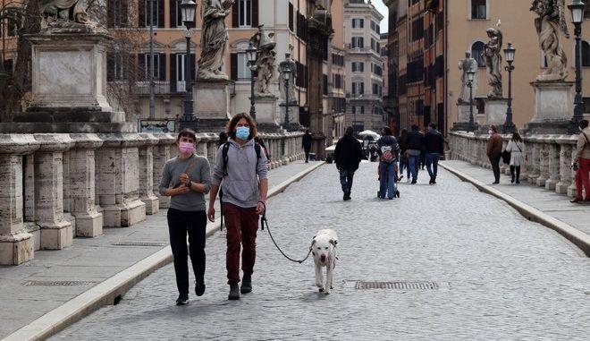 Κάτοικοι της Ρώμης περπατούν με μάσκα