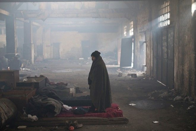 A man stands inside a disused railway warehouse used by refugees and migrants as shelter in Belgrade, Serbia, Thursday, Jan. 5, 2017.
