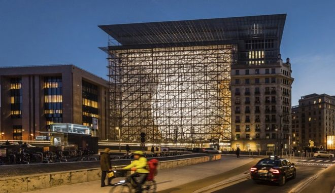 FILE - In this Friday, Dec. 9, 2016 file photo, a man rides a bike near the Europa building in Brussels. The newly opened Europa building is the headquarters of two institutions representing the EU member states: the Council of the European Union and the European Council. (AP Photo/Geert Vanden Wijngaert, File)