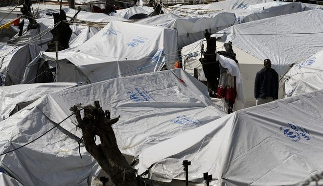In this photo taken on Thursday, March 16, 2017 an African migrant stands between tents at the Moria refugee detention center on the northeastern Greek island of Lesbos. The waters off northern Lesbos once resounded to the shrieks of the drowning, the whine of outboard motors as refugees struggled to reach Europe alive, and the thudding of rescue helicopter engines. A million people crossed the straits between Turkey and Greeces eastern Aegean islands in the year before March 20, 2016, and hundreds drowned. About half of those who made it landed on this island.  (AP Photo/Thanassis Stavrakis)
