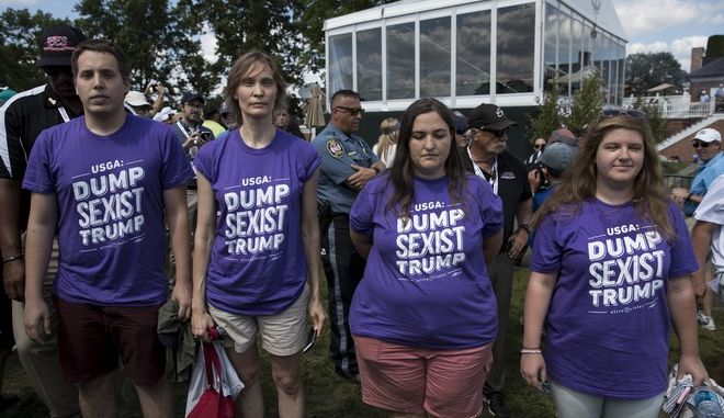 "Protesters with t-shirts that read ""USGA:Dump Sexist Trump"" position themselves near the presidential viewing stand, behind, where President Donald Trump is watching the U.S. Women's Open Golf tournament at Trump National Golf Club in Bedminster, N.J., Sunday, July 16, 2017. (AP Photo/Carolyn Kaster)"