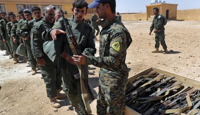 FILE - In this Thursday, July 20, 2017 file photo, Syrian Internal Security Forces receive weapons during their graduation ceremony, at Ain Issa desert base, in Raqqa province, northeast Syria. The spokesman for the U.S.-led coalition fighting the Islamic State says advances against the group in their stronghold of Raqqa have slowed(AP Photo/Hussein Malla, File)
