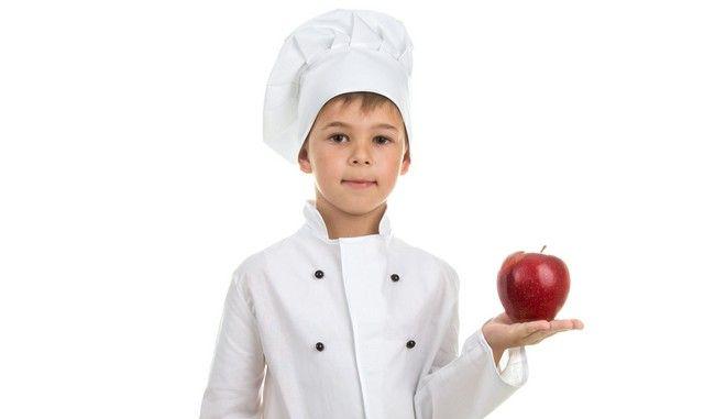 """Παιδί με """"στολή"""" σεφ που κρατά ένα μήλο."""