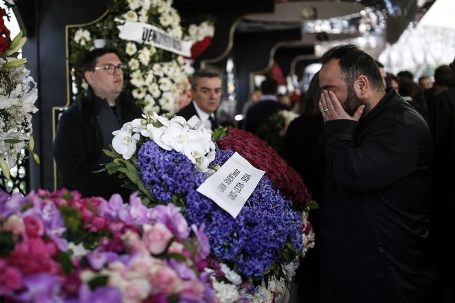 A man prays as family members gather around flower-covered coffin of Mina Basaran during funeral prayers in Istanbul, Thursday, March 15, 2018. Funerals have been held for nine out of the 11 victims from a private Turkish jet that crashed in Iran while flying a bride-to-be and her friends back to Istanbul from a bachelorette party in the United Arab Emirates. Mina Basaran, the 28-year-old daughter of the chairman of Turkey's Basaran Investment Holding, was killed along with her seven friends, and three female crew members.(AP Photo/Emrah Gurel)