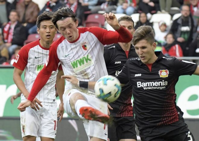 Augsburg's Michael Gregoritsch, left,  and Leverkusen's Panagiotis Retsos vie for the ball during the German Bundesliga soccer match between FC Augsburg and Bayer Leverkusen in Augsburg, Germany, Saturday, Nov. 4, 2017. (Stefan Puchner/dpa via AP)