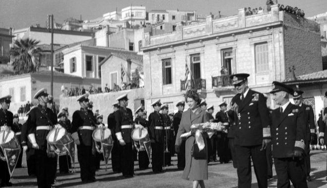 Britain's Princess Elizabeth is accompanied by King Paul of Greece, in dark glasses, as she passes the guard of honour and band after she had arrived at the small port of Tourkolimano, in Greece, on Dec. 6, 1950. She is to spend an unofficial six-day visit to Greece as the guest of the Greek King and Queen. (AP Photo)