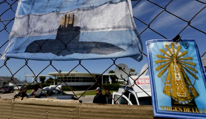 An Argentine national flag with a drawing of a submarine hangs from the fence surrounding the naval base in Mar del Plata, Argentina, Tuesday, Nov. 21, 2017. The search continues for the missing submarine, with 44 crew members, that has been lost for six days in the South Atlantic. (AP Photo/Vicente Robles)