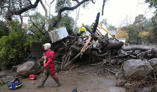 This photo provided by Stacey Wright with the Santa Barbara Urban Hikers shows rescue workers searching for survivors along Olive Mill Rd. Tuesday, Jan. 9, 2018, in Montecito, Calif. More than a dozen people were killed and homes were torn from their foundations Tuesday as downpours sent mud and boulders roaring down hills stripped of vegetation by a gigantic wildfire that raged in Southern California last month. (Stacey Wright/Santa Barbara Urban Hikers via AP)