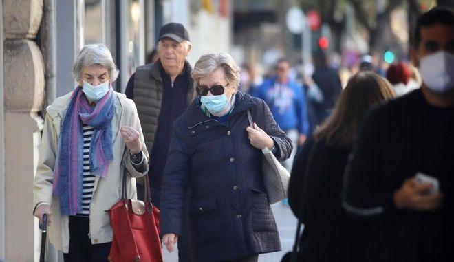 Πολίτες με μάσκες περπατούν στην πόλη