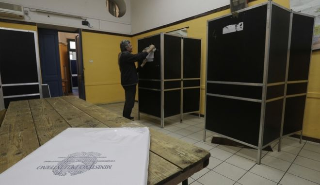 Janitor Gianni Morgia tags with a number a booth as he sets up a polling station for the March 4 general elections at the Pilo Albertelli high school in Rome, Friday, March 2, 2018. How the election plays out might well depend on the biggest bloc in the opinion polls: those saying they're undecided who will get their vote or if they'll even vote at all, along with those who say they'll boycott the vote. (AP Photo/Gregorio Borgia)