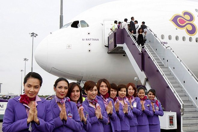 Thai Airways crew members pose beside the first Airbus Thai A380-800, bestowed with the royal name of