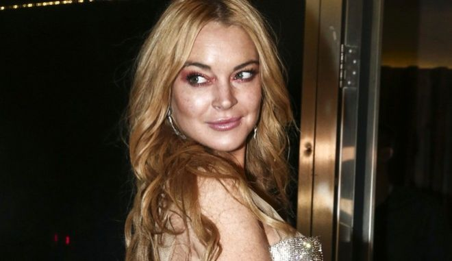 FILE - This Oct. 16, 2016 file photo shows actress Lindsay Lohan at the entrance of the Lohan Nightclub during the opening night in Athens, Greece. New York states highest court has agreed to allow Lohan to appeal her lawsuit against the makers of Grand Theft Auto, who the actress says used her likeness in the video game without permission. (AP Photo/Yorgos Karahalis, File)