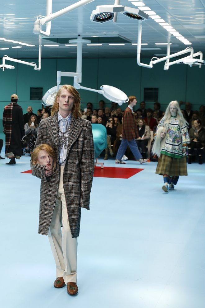 A model carries a fake head as he wears a creation as part of the Gucci women's Fall/Winter 2018-2019 collection, presented during the Milan Fashion Week, in Milan, Italy, Wednesday, Feb. 21, 2018. (AP Photo/Antonio Calanni)