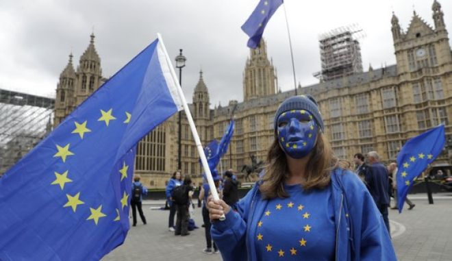 """A pro-remain supporter of Britain staying in the EU, wears an EU flag mask whilst taking part in a protest to coincide with politicians returning to work after the summer recess, outside the Houses of Parliament in London, Tuesday, Sept. 5, 2017. Britain's chief Brexit negotiator will face questions from lawmakers returning from summer recess Tuesday as the government plans to """"intensify"""" talks with the European Union. (AP Photo/Matt Dunham)"""