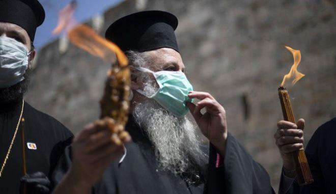 Ιερέας κρατά το κερί με το Άγιο Φως από τον Πανάγιο Τάφο