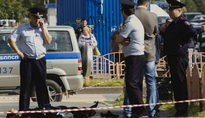 Police officers stand by the body of a man who was killed after an alleged stabbing attack, in the Siberian city of Surgut, Russia, Saturday, Aug. 19, 2017. A knife-wielding man went on a stabbing rampage in a Siberian city on Saturday, wounding seven people before police shot and killed him. (Irina Shvets/Siapress.ru via AP)
