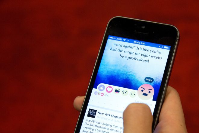 In this Thursday, Feb. 18, 2016 photo taken in New York, Julie Zhuo, product design director at Facebook, demonstrates the new emoji-like stickers customers will be able to press in addition to the like button. Facebook's Like button is getting some company, as the company rolls out alternatives worldwide after testing in a few countries. (AP Photo/Mary Altaffer)