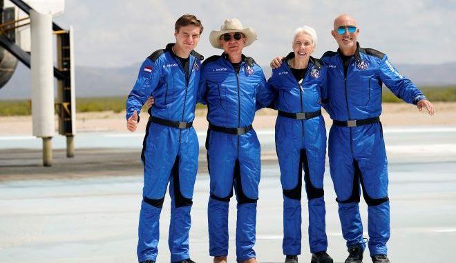 Ο Oliver Daemen, από αριστερά, ο Jeff Bezos, η Wally Funk και ο αδελφός του Bezos, Mark πόζαραν για φωτογραφίες μπροστά από τον πύραυλο Blue Origin.