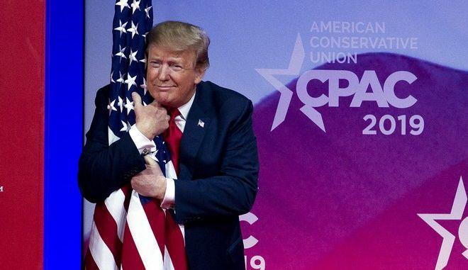 Ο Αμερικανός πρόεδρος Ντόναλντ Τραμπ αγκαλιάζει την σημαία των ΗΠΑ σε εκδήλωση του Συντηρητικού κόμματος