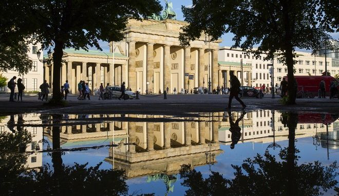 A man walks past a puddle reflecting Brandenburg Gate after rain showers in Berlin, Germany, Saturday, Aug. 6, 2016. (AP Photo/Gero Breloer)