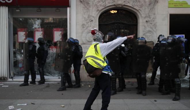 """Διαδηλωτής των """"Κίτρινων Γιλέκων"""", στέκεται μπροστά από τους αστυνομικούς"""