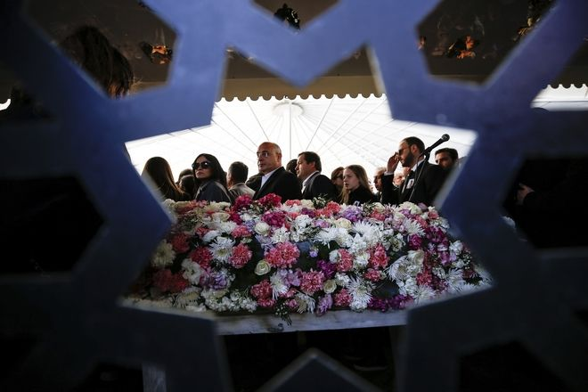 People gather around flower-covered coffin of Mina Basaran during funeral prayers in Istanbul, Thursday, March 15, 2018. Funerals have been held for nine out of the 11 victims from a private Turkish jet that crashed in Iran while flying a bride-to-be and her friends back to Istanbul from a bachelorette party in the United Arab Emirates. Mina Basaran, the 28-year-old daughter of the chairman of Turkey's Basaran Investment Holding, was killed along with her seven friends, and three female crew members.(AP Photo/Emrah Gurel)