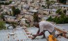 Άνδρας στην Αϊτή ασφαλίζει την οροφή του σπιτιού του λόγω της επερχόμενης καταιγίδας Έλσα, 3 Ιουλίου 2021.