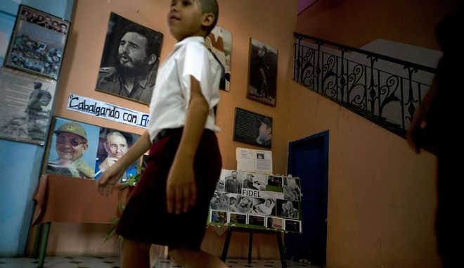A students walks past an exhibit of photographs of Cuba's late leader Fidel Castro at school in Havana, Cuba, Friday, Nov. 24, 2017. The anniversary of Fidel Castro's death will be marked on Saturday, Nov. 25. (AP Photo/Ramon Espinosa)