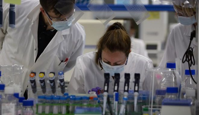Lab technicians speak with each other during research on coronavirus, COVID-19, at Johnson & Johnson subsidiary Janssen Pharmaceutical in Beerse, Belgium, Wednesday, June 17, 2020. Janssen Pharmaceutical hopes to begin clinical trials on a potential vaccine for COVID-19 in the middle of the summer. (AP Photo/Virginia Mayo)