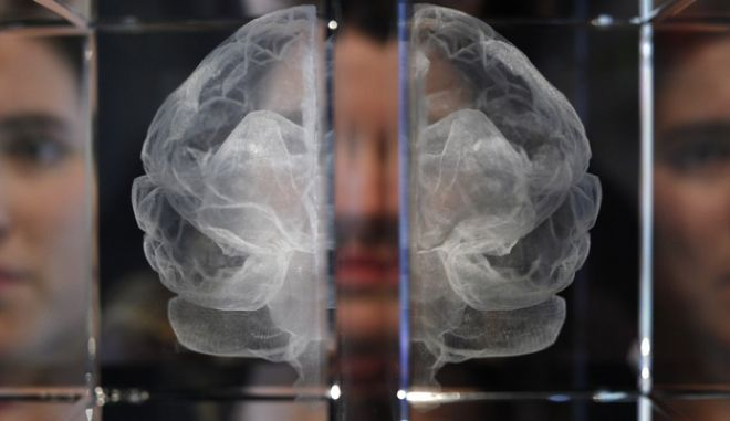 Wellcome Trust employee Zoe Middleton poses for the media by a work entitled 'My Soul' by artist Katherine Dawson, that is a laser etched in lead crystal glass of the artist's own MRI scan, at an exhibition call 'Brains -The Mind as Matter' at the Wellcome Collection in London, Tuesday, March, 27, 2012. The free exhibition is open to the public from March 29- June 17. (AP Photo/Alastair Grant)