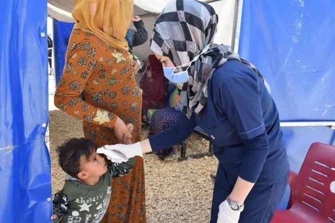 Νοσοκόμα με μάσκα προσπαθεί να φροντίσει ένα παιδί