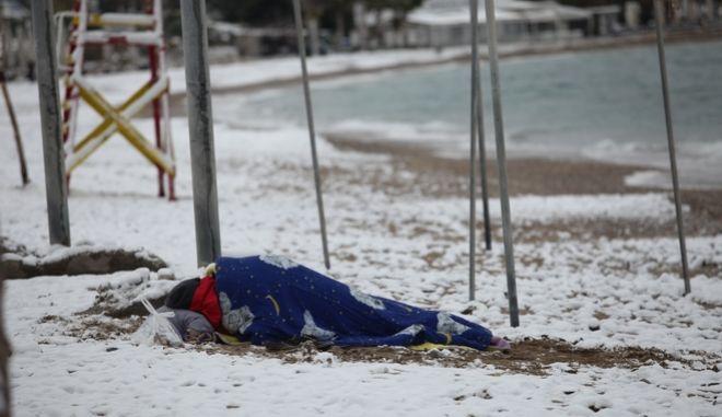 Άστεγος κοιμάται σε παραλία του Παλαιού Φαλήρου κατα την διάρκεια της χιονόπτωσης την Τρίτη 10 Ιανουαρίου 2017. (EUROKINISSI/ΓΙΑΝΝΗΣ ΠΑΝΑΓΟΠΟΥΛΟΣ)