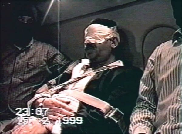 LON97:OCALAN-CAPTURE-FOOTAGE:ISTANBUL,17FEB99 - Captured Kurdish rebel leader Abdullah Ocalan sits in a seat aboard a private aircraft bound and blindfolded and flanked by special forces February 15 following his removal from the Greek embassy in Nairobi. Turkey said on Wednesday that rival Greece's hosting of captured Kurdish rebel leader was a 'grave event' and Athens had misled Ankara over its support for guerrillas.   ws/Turkish TV    REUTERS