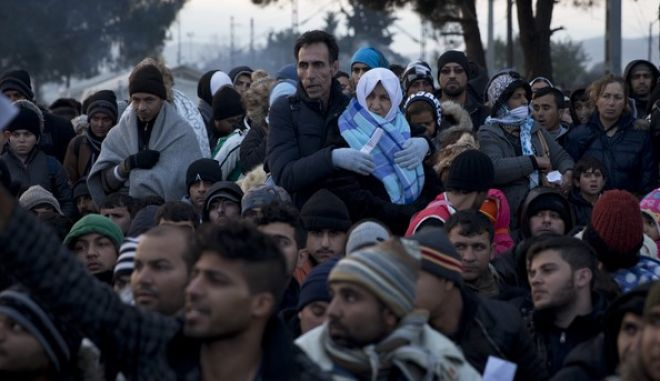 Refugees wait to be allowed to cross into Macedonia at the northern Greek border station of Idomeni, Saturday, Dec. 5, 2015. Greece has been the main point of entry into the EU for about 700,000 migrants and refugees so far this year.(AP Photo/Petros Giannakouris)